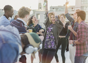 Playful young adult friends dancing at rooftop party - CAIF16144