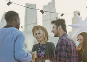 Young adult friends talking and drinking at rooftop party - CAIF16150