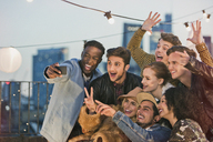 Enthusiastic young adult friends cheering and taking selfie at rooftop party - CAIF16153