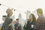 Young adult friends drinking and talking at rooftop party - CAIF16156