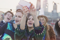 Young women laughing and taking selfie at rooftop party - CAIF16168