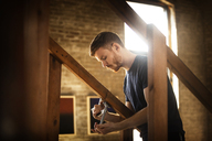 Side view of man adjusting clamp on wooden railing at home - CAVF07892