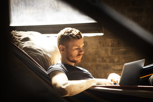 Man using laptop computer while relaxing in hammock - CAVF07895