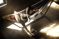 Overhead view of man wearing hat using laptop computer while sitting in hammock tied on stand - CAVF07901