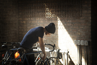 Man looking at bicycle in rack - CAVF07910