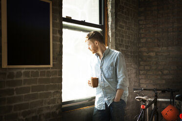 Man with hand in pocket holding coffee cup while standing by window at home - CAVF07934
