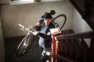 High angle view of man carrying bicycle on stairs at home - CAVF07940