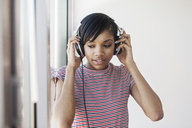 Woman looking away while wearing headphone at home - CAVF07961