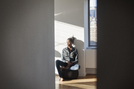 Young woman looking away while sitting at home - CAVF07970