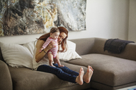 Mother teaching baby girl to walk while sitting on sofa at home - CAVF07982