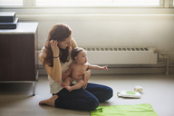 Mother sitting with daughter at home - CAVF07988