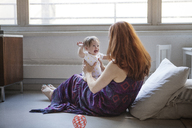 Woman playing with daughter while sitting at home - CAVF08015