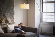 Woman relaxing on sofa at home - CAVF08021