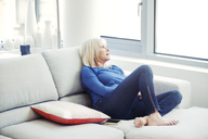 Senior woman relaxing on sofa at home - CAVF08066