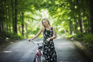 Smiling woman with bicycle walking on road - CAVF08087