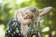 Woman looking away while leaning on bicycle handle - CAVF08090