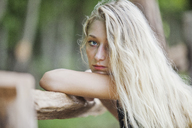 Portrait of woman leaning on wooden fence - CAVF08093