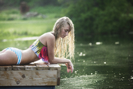 Woman looking in water while relaxing on pier at lake - CAVF08099