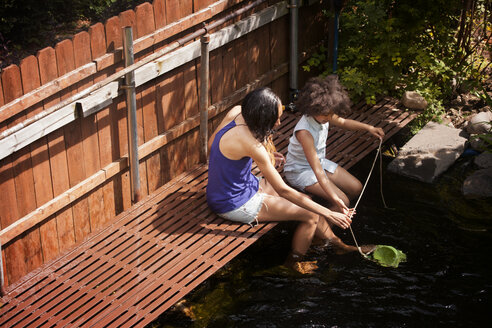 Mother and daughter sitting on footbridge over pond in backyard - CAVF08114