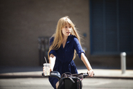 Woman looking away while cycling on road in city - CAVF08138