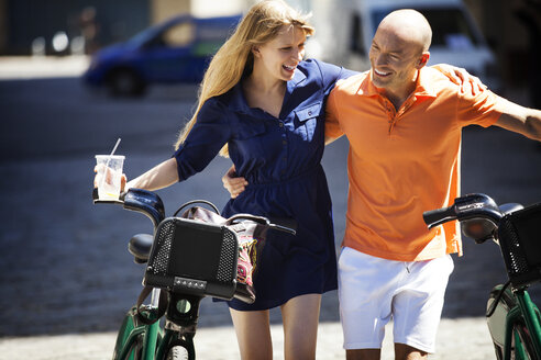 Smiling couple with bicycle walking on road in city - CAVF08141
