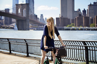Woman with bicycle standing against Brooklyn Bridge - CAVF08144