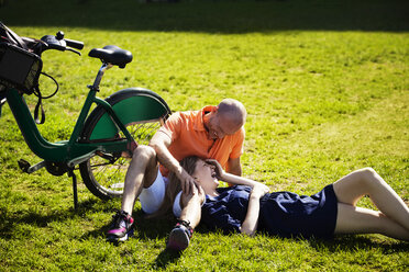 Cheerful couple relaxing on grassy field - CAVF08147