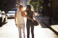 Rear view of couple with arms around walking on street in city - CAVF08150