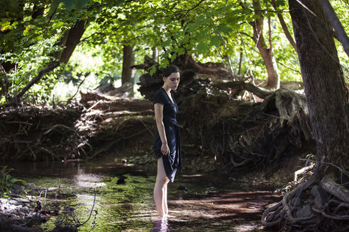 Teenage girl standing in stream at forest - CAVF08186
