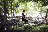 Teenage girl sitting on fallen tree trunk at forest - CAVF08189