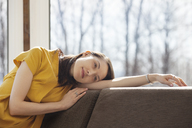 Smiling woman relaxing on sofa at home - CAVF08192