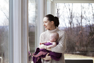 Thoughtful woman carrying baby girl while looking through window at home - CAVF08204