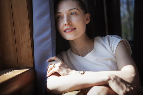 Smiling woman looking through window while sitting at home - CAVF08222