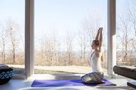 Side view of woman practicing yoga at home - CAVF08237