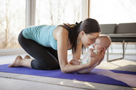 Loving mother holding baby girl while kneeling on exercise mat - CAVF08246