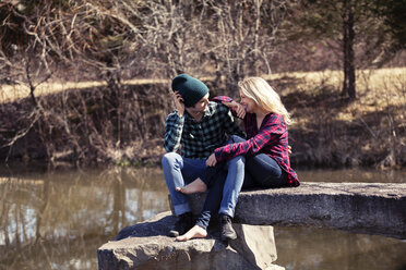 Happy couple talking while sitting on rock by lake - CAVF08264