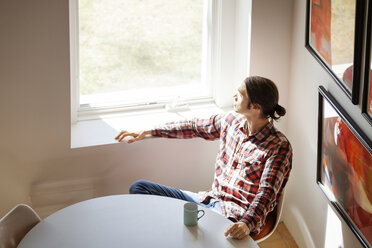 Overhead view of thoughtful man sitting by window at home - CAVF08270