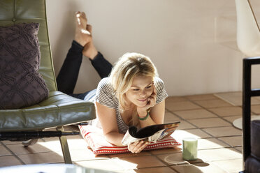 Smiling woman reading magazine while lying on floor at home - CAVF08273