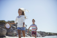 Young girl and boy running along beach - CAIF16288