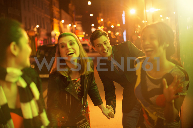 Friends walking down city street together at night - CAIF16297