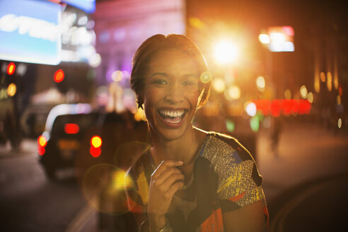 Woman smiling on city street at night - CAIF16300