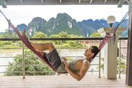Laos, Vang Vieng, young man lying in hammock using laptop - AFVF00298