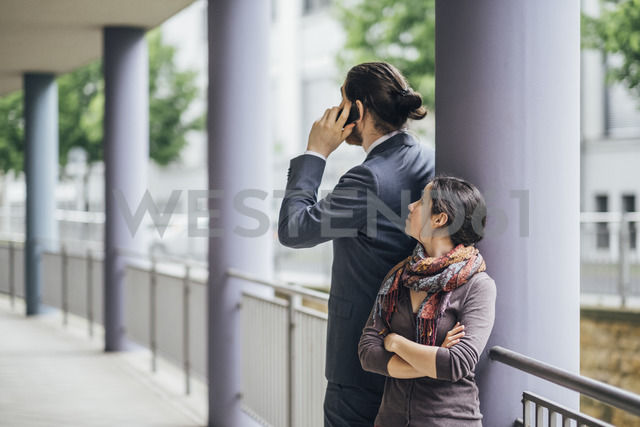 Woman looking at businessman talking on cell phone - JSCF00064