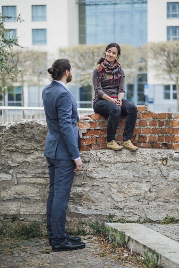 Woman sitting on a wall outside office building smiling at businessman - JSCF00067 - Jonathan Schöps/Westend61