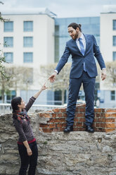 Businessman standing on a wall reaching out his hand for woman - JSCF00070