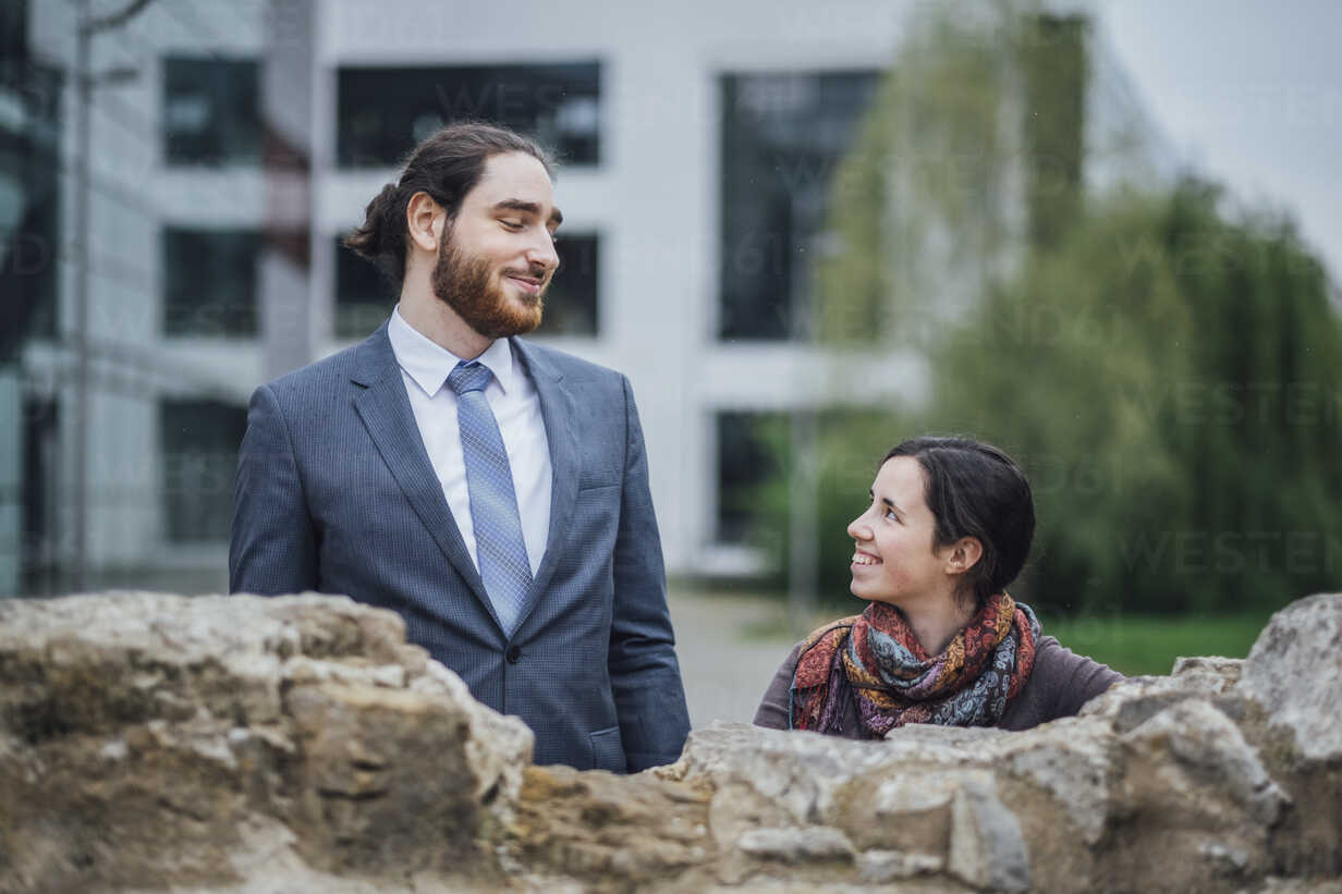 Smiling businessman and woman behind a wall outside office building - JSCF00073 - Jonathan Schöps/Westend61