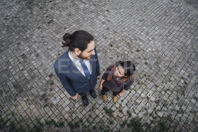 Woman and businessman standing on cobblestones smiling at each other - JSCF00076