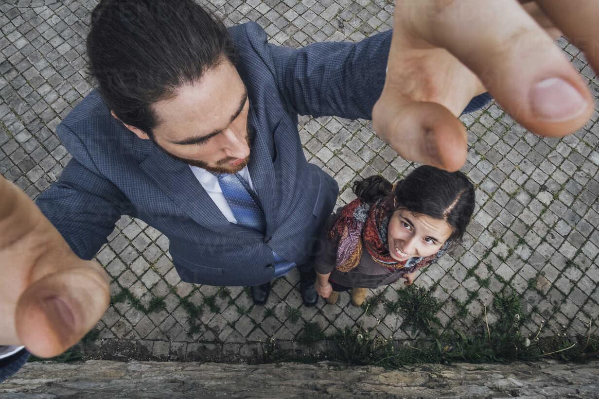 Tall businessman standing on cobblestones beside small woman - JSCF00079 - Jonathan Schöps/Westend61