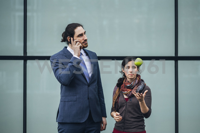 Businessman talking on cell phone and woman throwing an apple - JSCF00082