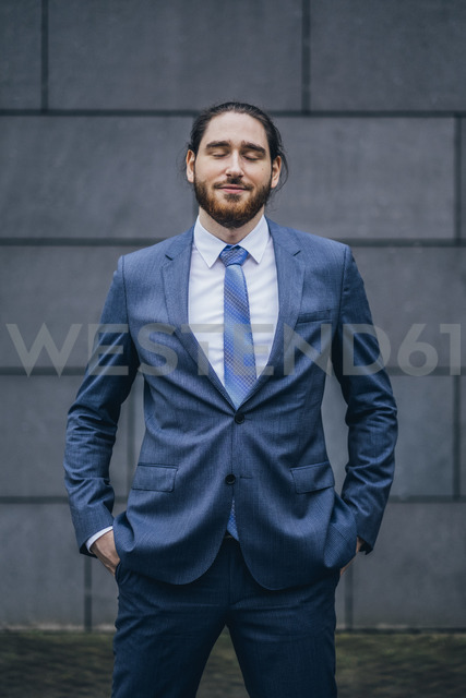 Portrait of smiling businessman standing outdoors with closed eyes - JSCF00088 - Jonathan Schöps/Westend61